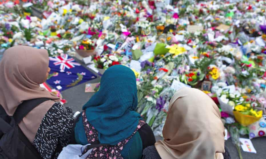 Women stand looking at piles of flowers left in tribute to the people who died in terrorist attacks in Christchurch.