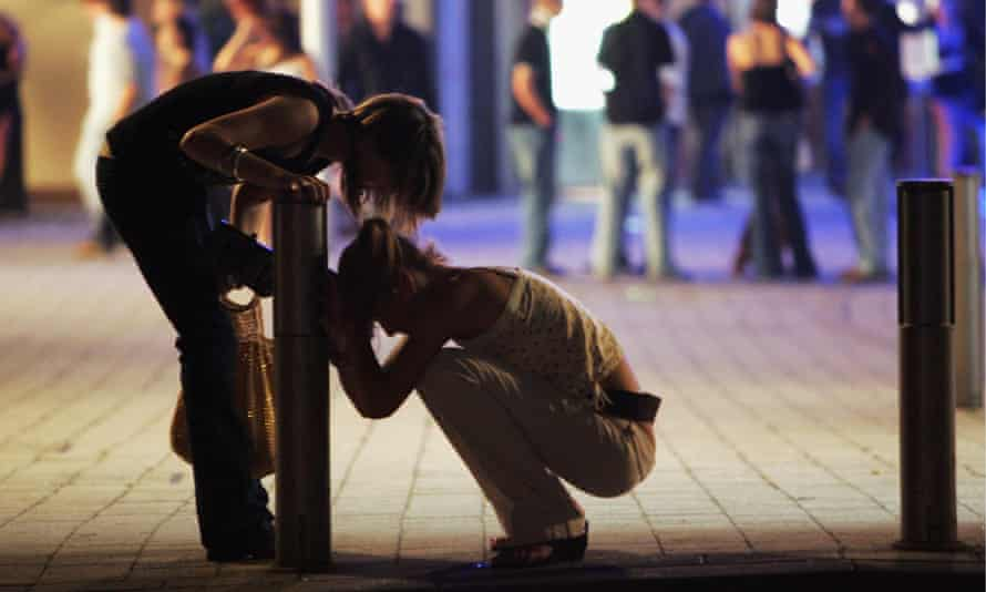 A reveller stops to help her friend after leaving a bar in Bristol City Centre on October 15, 2005 in Bristol, England