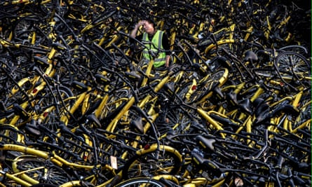 A Chinese mechanic from bike share company Ofo stands amongst a pile of thousands of damaged bicycles in need of repair.