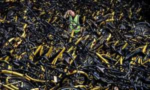 A mechanic from the bike-share company Ofo Inc stands in a Beijing repair depot among thousands of damaged bicycles that were pulled off the streets