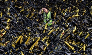A mechanic from bike share company Ofo amongst a pile of damaged bicycles in Beijing.