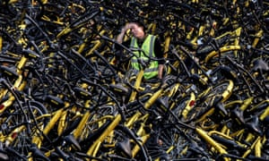 A Chinese mechanic from Ofo among a pile of thousands of damaged bicycles in need of repair.