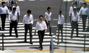 Office workers cross a street during lunch hour in Tokyo