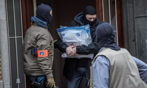 Belgian police carry out bags of evidence from a house in the district of Anderlecht-Brussels, during a police raid