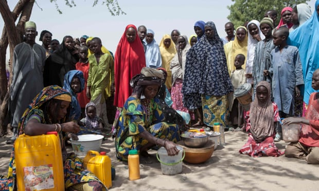 Local cereal vendors are seen with displaced people at an IDP camp in Dikwa, Borno state, Nigeria