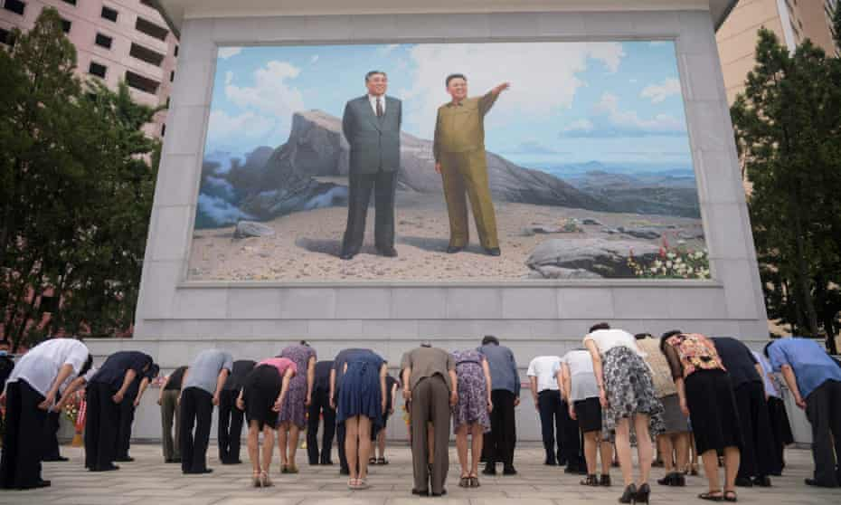 People bow before a mosaic of portraits of late North Korean leaders Kim Il Sung and Kim Jong Il