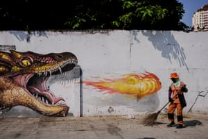 Jakarta: a worker cleans up the road in front of a mural