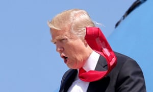 Donald Trump's tie flaps in the wind, revealing sticky tape attached to the back, as he arrives at Orlando international airport on 3 March 2017.