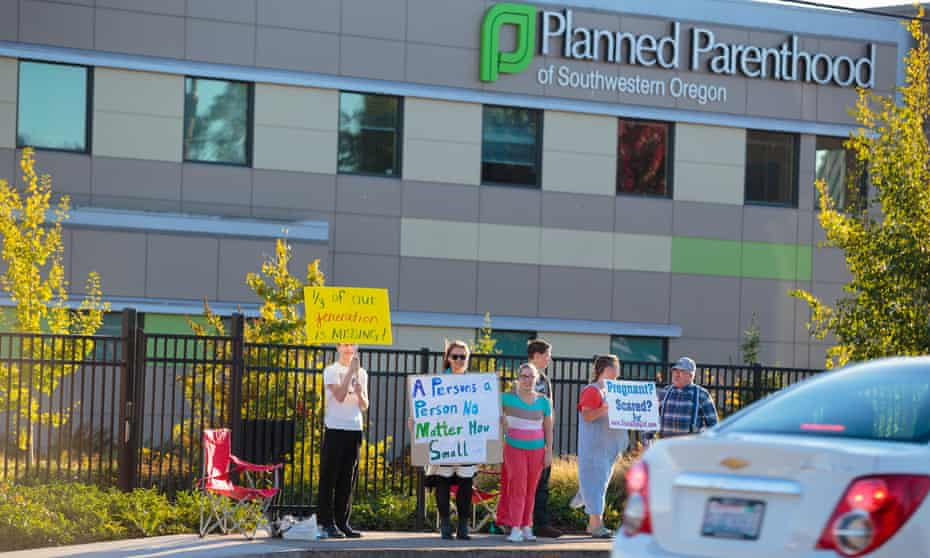 Anti-abortion protesters target pedestrian and vehicle passersby in front of a Planned Parenthood facility.