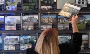 A woman looking at houses for sale in an estate agents in Edinburgh