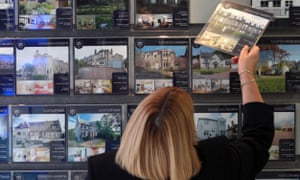 A woman looks at properties for sale in an estate agents in Edinburgh