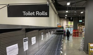 A shopper passes empty shelves usually stocked with toilet paper in a supermarket in Melbourne.