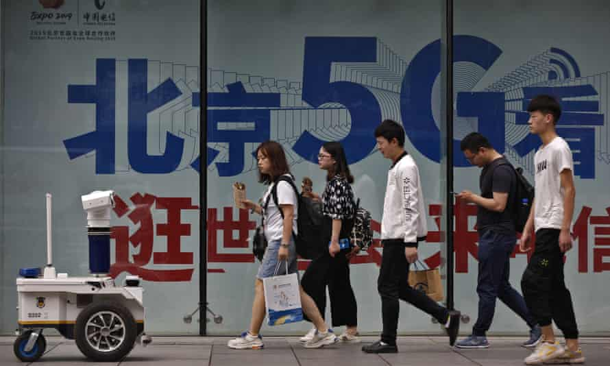 People walk toward a police robot mounted with surveillance cameras patrol past a 5G network advertisement