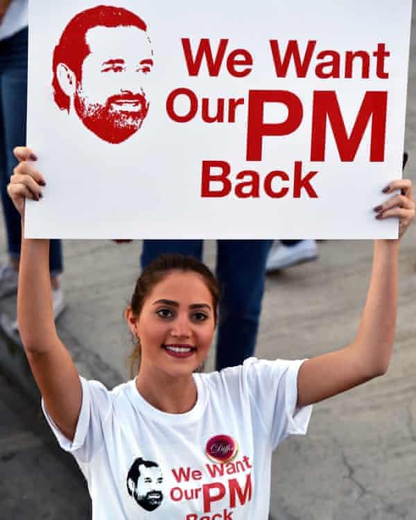 A woman demands the return of Saad Hariri from Saudi Arabia during the Beirut marathon on 12 November.