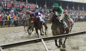 Kent Desormeaux aboard Exaggerator wins in the Pimlico mud.