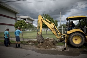 Aqueduct and sewer authority workers in Guanica work with a broken water pipe