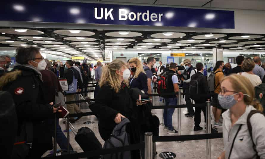 People queueing at Heathrow under a 'UK Border' sign