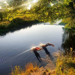 Two swimmers dive into a river as sunlight hits the water