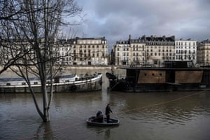 People use a small boat to leave a barge moored on the Seine