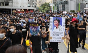 A marcher's sign reads 'Carrie Lam condemned by history'