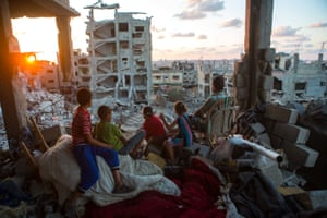 Palestinian family members sit in their home, which was destroyed during Operation Protective Edge (Tsuk Eitan), in al-Tuffah district in Gaza City.