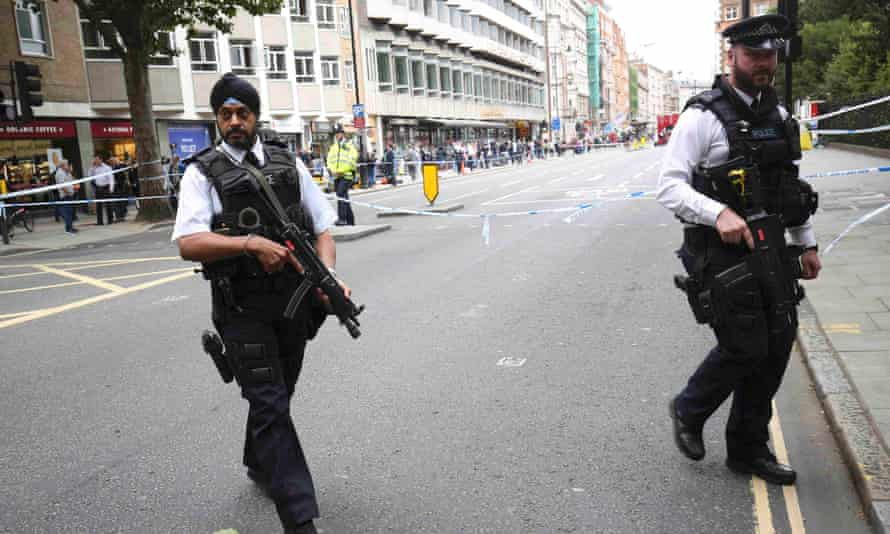 Armed police officers patrol at the scene of a knife attack in Russell Square in London.