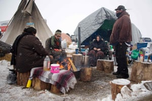 Activists sit around a camp fire as it snows at Oceti Sakowin camp .
