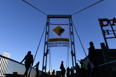 Two activists unveil a banner protesting coal financing by the Commonwealth Bank in Sydney in May.