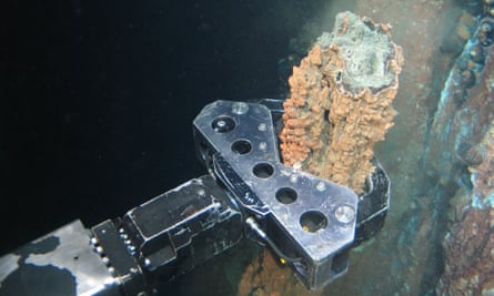 A robotic arm breaks off a chunk of mineral-rich rock for sampling deep underwater off the coast of Papua New Guinea.