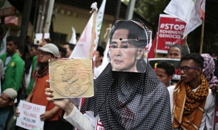 A Muslim woman wears an Aung San Suu Kyi mask during a rally against the persecution of Rohingya.