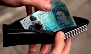 A person is pictured holding a wallet containing a £5 note