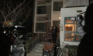 Li Wenzu (left) waits to leave her apartment building in Beijing on Boxing Day to try to attend her husband's trial.