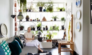 Rhonda Drakeford in her living room with plants on shelving the length of the windowed end wall