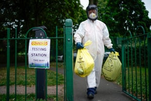 A city council worker carries rubbish from a coronavirus testing centre at Spinney Park on 29 June, 2020 in Leicester, England.