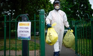 A city council worker carrying bags of rubbish at a coronavirus testing centre at Spinney Park in Leicester.