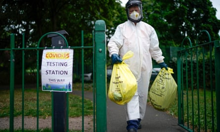 A city council worker carries rubbish from a coronavirus testing centre in Leicester.