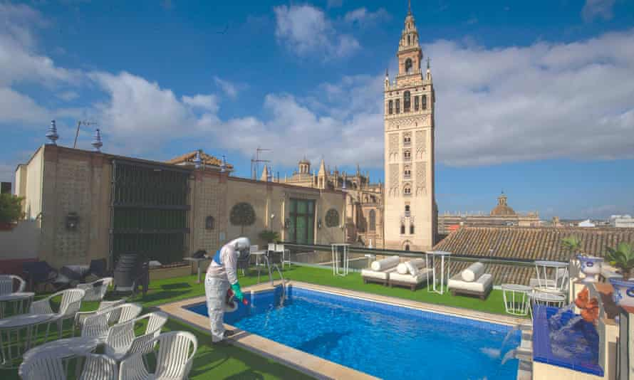 A worker desinfecting the terrace of hotel in Seville,.
