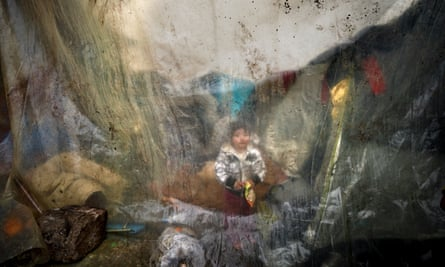 A child shelters from the rain under plastic sheeting in the refugee camp at Idomeni on Greece's northern border, in 2016.