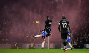 Christian Benteke emerges from the smoke in the Crystal Palace end to win a header during the grudge match between Brighton.