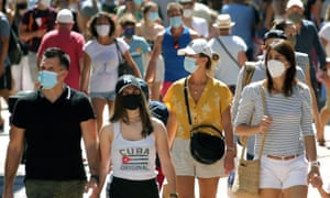 People wearing face masks to protect against coronavirus, walk down the street, in Saint Jean de Luz, south-western France, on Wednesday. Since Monday, 69 towns in western France imposed outdoor mask rules to slow the spread of coronavirus.