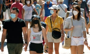 People wearing face masks to protect against coronavirus walk down the street in Saint Jean de Luz, southwestern France.