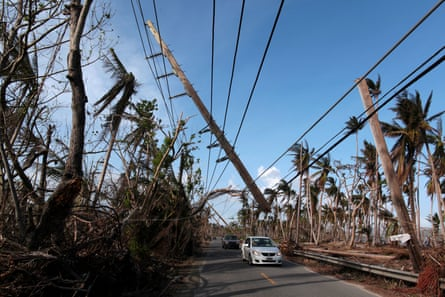 Cars drive under a partially collapsed utility pole after the island was hit by Hurricane Maria.