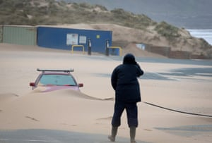 A car is covered by sand at Fistral beach car park, Newquay, Cornwall