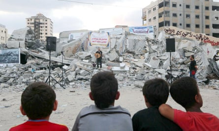 Can the show go on? Amusician performs amid the rubble of Said al-Mishal Cultural Center, Gaza City, last week.