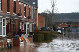 People empty out buckets of water from the front yard of a flooded property after the River Wye burst its banks in Ross-on-Wye on 17 February 17, in the aftermath of Storm Dennis