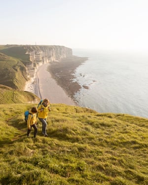 France, Normandy: Mother and son in yellow jackets hiking on cliffs covered with grass above the beach of Etretat