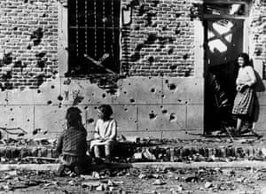 Madrid, 1936Children, unaware of the horror of war, play in front of the shrapnel-hit facade of No 10 Peironcely street. November-December 1936