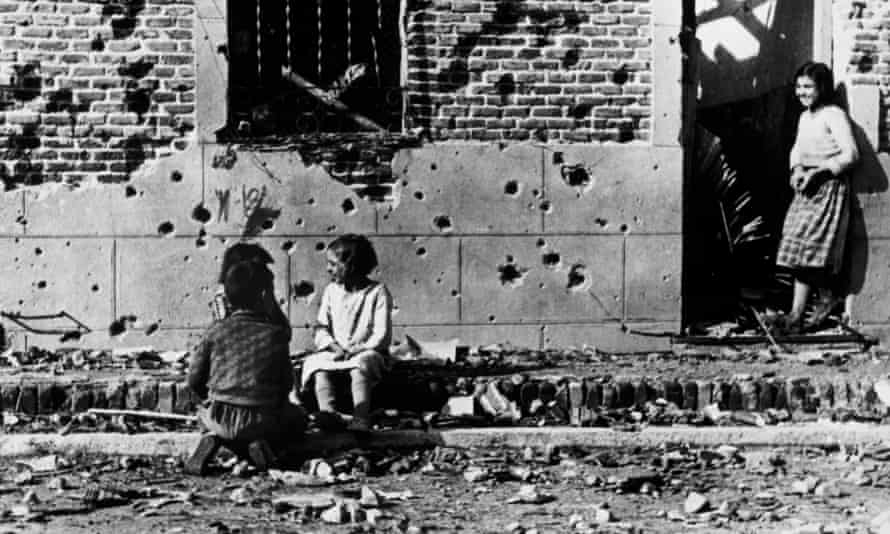 Children, unaware of the horror of war, play in front of the shrapnel-hit facade of No 10 Peironcely street, Madrid. November-December 1936.