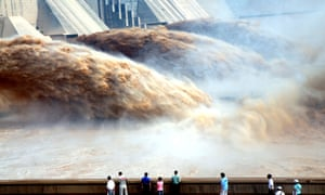 Tourists watch floodwaters gushing out of the Xiaolangdi dam during a sand-washing operation of the Yellow river in Jiyuan, China, 2010.