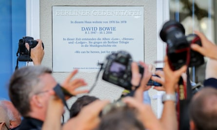 People take photos of a commemorative plaque for David Bowie in Berlin.